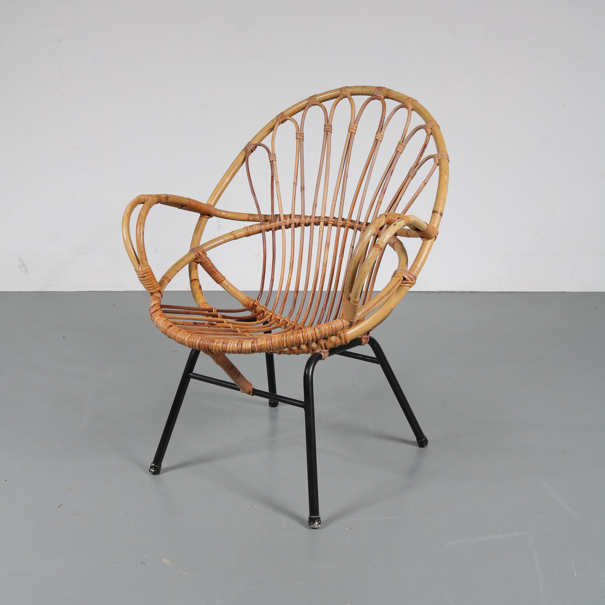 m22428 1950s Round rattan chair with armrests on black metal base Gebroeders Jonkers / Netherlands