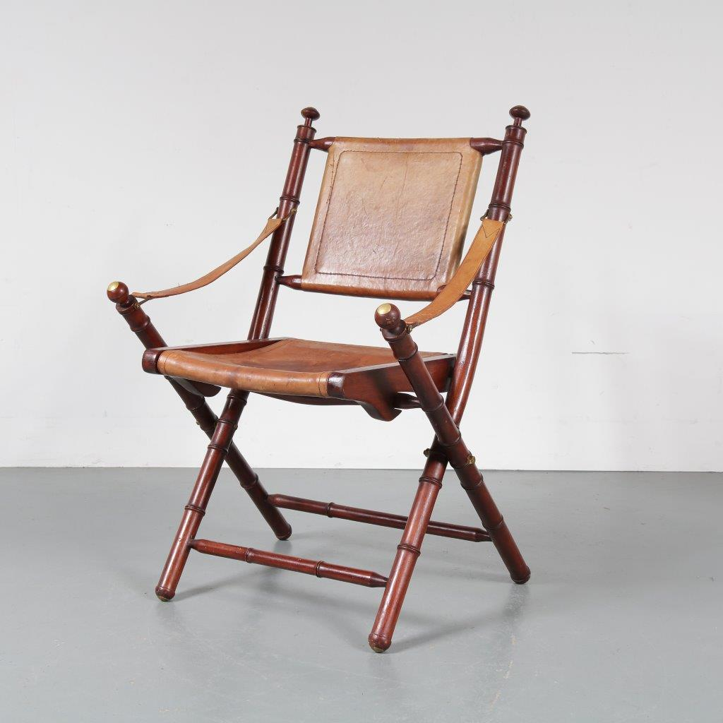 m22897 1970s Regent style wooden folding chair with cognac leather upholstery and brass details
