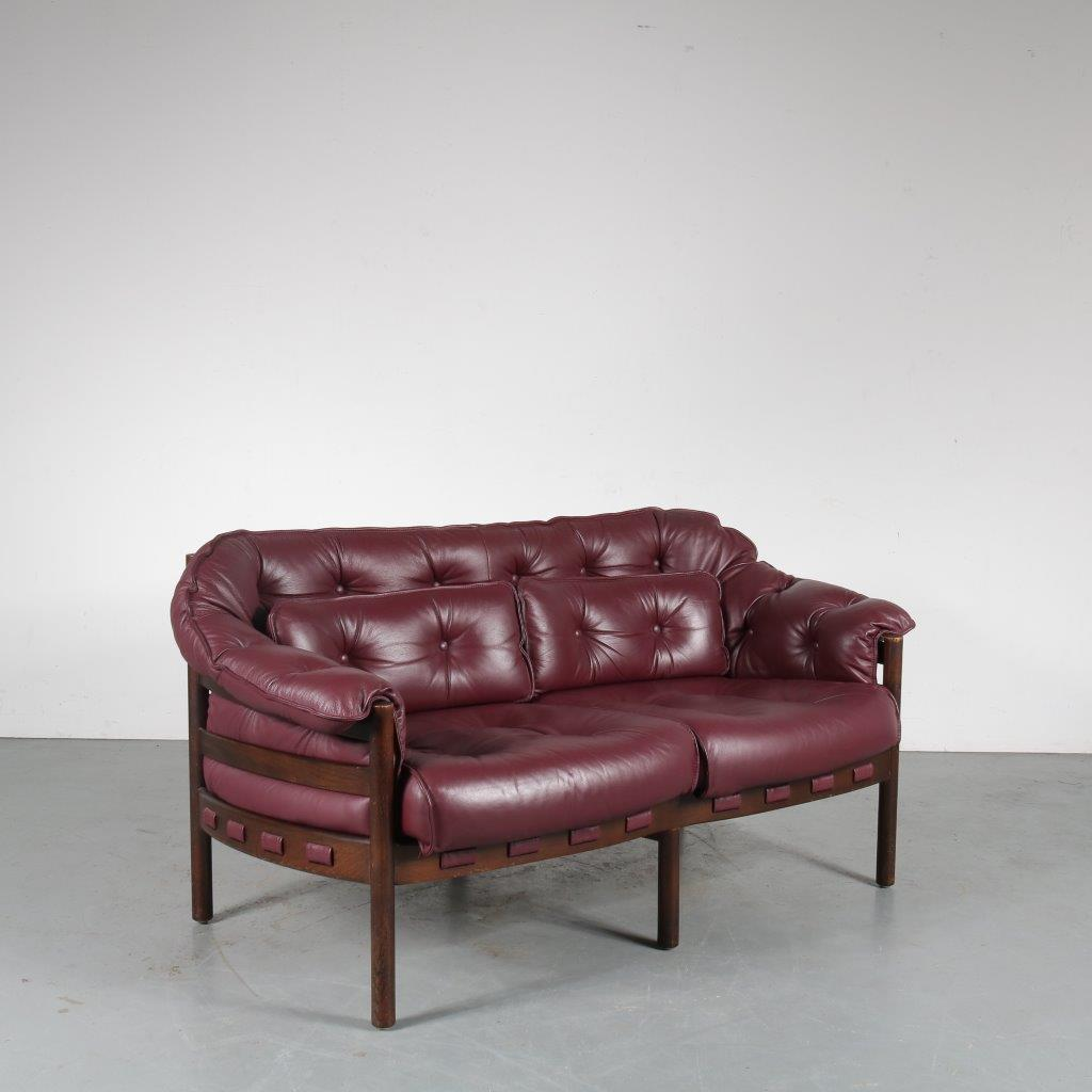 m23867 1960s Two-seater sofa on dark wooden frame with bordeaux red leather upholstery Arne Norell Coja / Netherlands